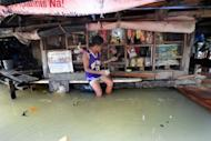 A boy is seen making a purchase at a flooded convinient store in Manila on August 15. Tropical Storm Kai-tak blew out of the Philippines on Thursday, offering some relief for millions of people struggling to recover from a brutal few weeks of monsoon rains that claimed 109 lives