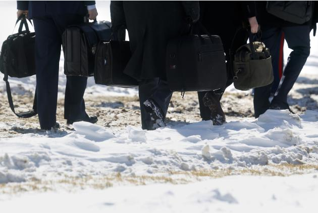 Staff members and military aides to Obama walk through the snow to board the Marine One helicopter for travel with the president from the White House in Washington