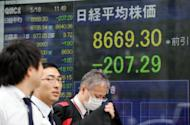 File photo of a prices screen in Tokyo flashing the level of the Nikkei index. Asian markets sank Wednesday on growing concerns that Spain could be forced into seeking a bailout while China dashed previous hopes it will introduce fresh stimulus measures to boost its economy