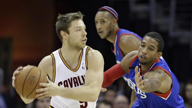 Cleveland Cavaliers' Matthew Dellavedova, left, from Australia, looks to pass under pressure from Philadelphia 76ers' Darius Morris during the first quarter of an NBA basketball game Saturday, Nov. 9, 2013, in Cleveland