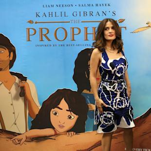 "Mexican-American actress Salma Hayek poses for photographers next to a poster for the film, ""The Prophet,"" an animated feature film she co-produced, on her arrival to a cinema where she gave a press conference, in Beirut, Lebanon, Monday, April 27, 2015. In her first visit to her ancestral homeland, Hayek, whose paternal grandfather was Lebanese and immigrated to Mexico, visited the picturesque mountain village of Bcharre in northern Lebanon on Sunday to pay homage to Khalil Gibran, the Lebanese-born poet who wrote ""The Prophet,"" the book on which the film is based. (AP Photo/Hussein Malla)"