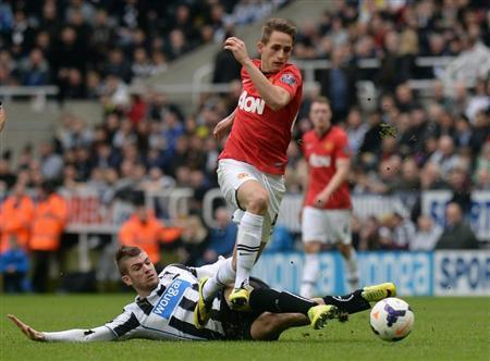 Manchester United's Januzaj is challenged by Newcastle United's Davide Santon during their English Premier League soccer match at St James' Park in Newcastle