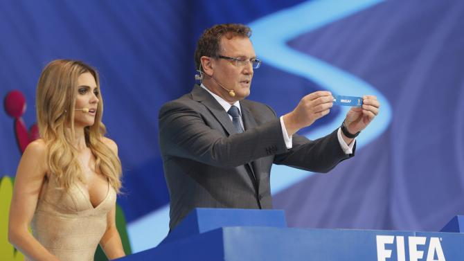 "Valcke holds up the slip showing ""Uruguay"" during the draw for the 2014 World Cup in Sao Joao da Mata"