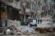 Civilians carry their belongings along a street strewn with garbage and debris following fighting between Syrian government troops and rebel fighters in the Salaheddin district of Aleppo. Syria's army and main rebel force said they will cease fire on Friday, in line with an internationally backed truce during a Muslim holiday, but both reserved the right to respond to any aggression