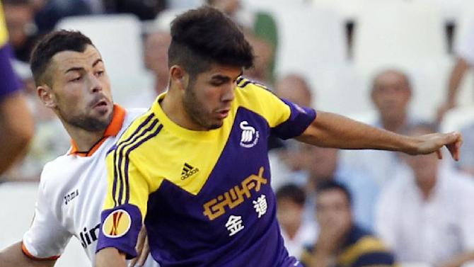 Swansea City's  Alejandro Pozuelo from Spain duels for the ball with Valencia's Javi Fuego  during their  Europa  League Group A soccer match at the Mestalla stadium in Valencia, Spain, Thursday , Sept. 19, 2013
