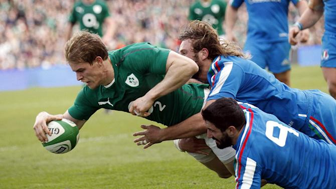 Ireland's Andrew Trimble scores a try despite being tackled by Italy's Tito Tebaldi, right, and Joshua Raffaele Furno during their Six Nations Rugby Union international match at the Aviva Stadium, Dublin, Ireland, Saturday, March 8, 2014. (AP Photo/Peter Morrison)
