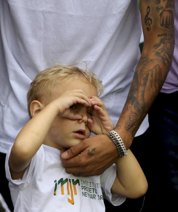 """Davi Lucca, son of Barcelona and Brazilian national soccer player Neymar, reacts as his father talks to media during a """"World Boots"""" event for children with disabilities, at the Neymar Insti"""