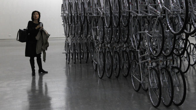 "A visitor stands at an instillation entitled ""Forever Bicycles"" by the Chinese artist and activist Ai Weiwei at the ""Ai Weiwei is Absent"" exhibition in the Taipei Fine Arts Museum in Taipei, Taiwan, Friday, Oct. 28, 2011. (AP Photo/Wally Santana)"