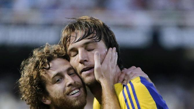 Swansea City's Michu from Spain, right, is congratulated by teammate Jose Canas from Spain, left, after scoring a goal against Valencia during their Europa League Group A soccer match at the Mestalla stadium in Valencia, Spain, Thursday, Sept. 19, 2013