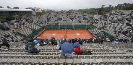 Tennis - French Open - Roland Garros - Spectators protect themselves from the rain