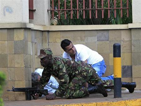 A Kenyan army soldier takes cover behind a wall at Westgate Shopping Centre in Nairobi September 21, 2013. REUTERS/Noor Khamis
