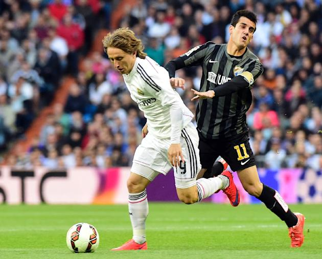 Real Madrid's Croatian midfielder Luka Modric (L) vies for the ball during the Spanish league football match Real Madrid vs Malaga at the Santiago Bernabeu stadium in Madrid on April 18, 2015