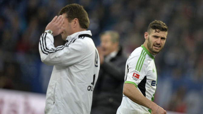 Wolfsburg's Daniel Caligiuri, right, passes his coach Dieter Hecking after he got the red card during the German Bundesliga soccer match between FC Schalke 04 and VfL Wolfsburg in Gelsenkirchen,  Germany, Saturday, Feb. 1, 2014. Schalke defeated Wolfsburg  by 2-1