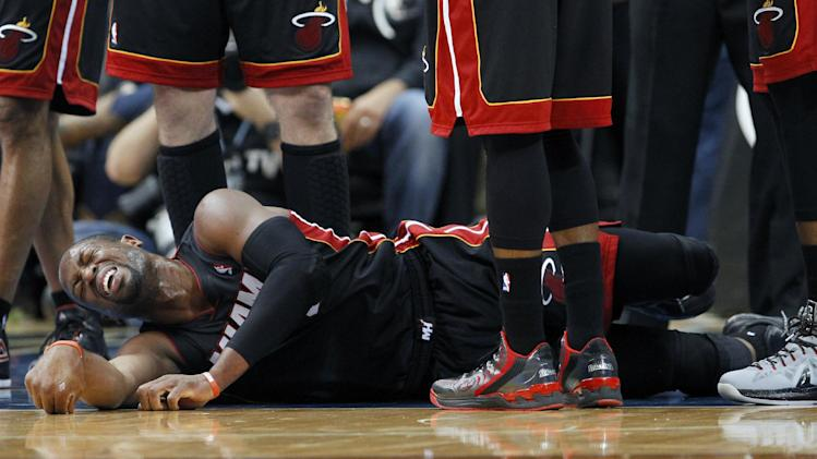 Miami Heat guard Dwyane Wade reacts after landing hard on his right knee during the first quarter of an NBA basketball game against the Minnesota Timberwolves in Minneapolis, Saturday, Dec. 7, 2013.Wade stayed in the game and scored 19 points as the Heat won 103-82