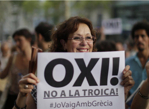 "A woman holds a banner reading,  ""No to the Troika, I support  Greece"" during a a pro Greece demonstration at the European Union office in Barcelona, Spain, Friday, July 3, 2015. A new opini"