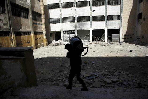 A rebel fighter of 'Abu Amara Brigades' carries a homemade shell as he walks inside a damaged school at the frontline against forces loyal to Syria's President Bashar al-Assad in Aleppo&#3