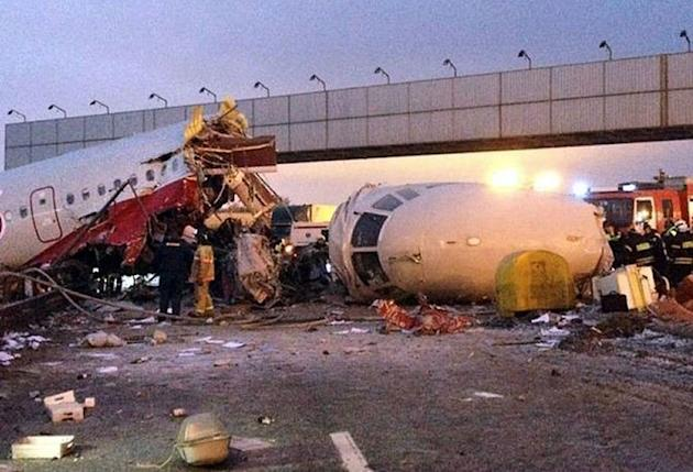 Police investigators and emergency services teams work at the Tu-204 jet crash site near the Vnukovo international airport outside Moscow on December 29, 2012. Four crew were killed on Saturday when the Russian airliner crashed into a motorway and broke up into three pieces after overshooting the runway