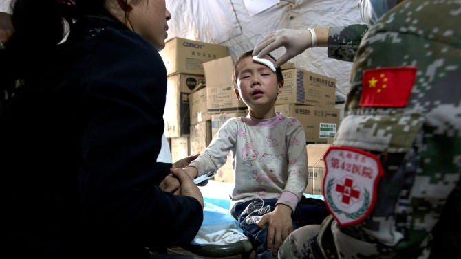 A child gets treatment in a military field hospital in the county seat of Lushan in Sichuan province, China, Monday, April 22, 2013. The efforts under way in the mountainous province after a quake Saturday that killed nearly 200 people showed that the government has continued to hone its disaster reaction — long considered a crucial leadership test in China — since a much more devastating earthquake in 2008, also in Sichuan, and another one in 2010 in the western region of Yushu. (AP Photo/Ng Han Guan)