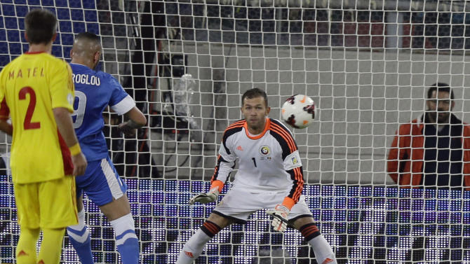 Greece's Kostas Mitroglou, center, scores the opening goal against Romania's goalkeeper Bogdan Ionut Lobont during their World Cup qualifying playoff first leg soccer match at the Karaiskaki stadium in the port of Piraeus, near Athens, Friday, Nov. 15, 2013