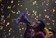 Confetti drops as a Filipino blows his paper horn as they welcome the New Year at Manila's Rizal Park, Philippines on Sunday Jan. 1, 2012. More than 200 people have been injured by illegal firecrackers and celebratory gunfire in the Philippines despite a government scare campaign against reckless New Year revelries, officials recently said. (AP Photo/Aaron Favila)