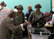 Egyptian soldiers stand guard next to a ballot box as an elderly man casts his vote in the second round of the historical presidential election at a polling station in the city of Zagazig. Egyptians voted on Saturday in a run-off presidential election pitting an Islamist against Hosni Mubarak's last premier as the military rulers entered a showdown with the Islamists by disbanding parliament