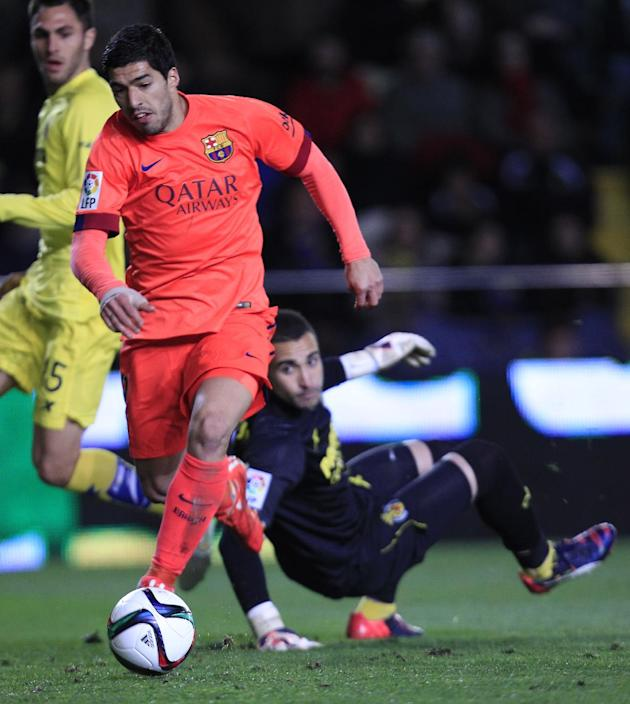 Barcelona's Luis Suarez, left, shoots to score pass Villarreal's goalkeeper Sergio Asenjo during a semifinal, second leg, Copa del Rey soccer match between FC Barcelona and Villarreal at the M