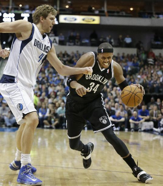 Brooklyn Nets forward Paul Pierce (34) drives against Dallas Mavericks forward Dirk Nowitzki (41) of Germany during the first half of an NBA basketball game Sunday, March 23, 2014, in Dallas