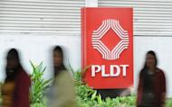 Pedestrian pass by the logo of of Philippine Long Distance Telephone co. (PLDT) in Makati City suburban Manila in May 2012. PLDT on Tuesday posted an 11 percent drop in second-quarter profit from a year earlier due to the costs of modernising its networks in a fiercely competitive market