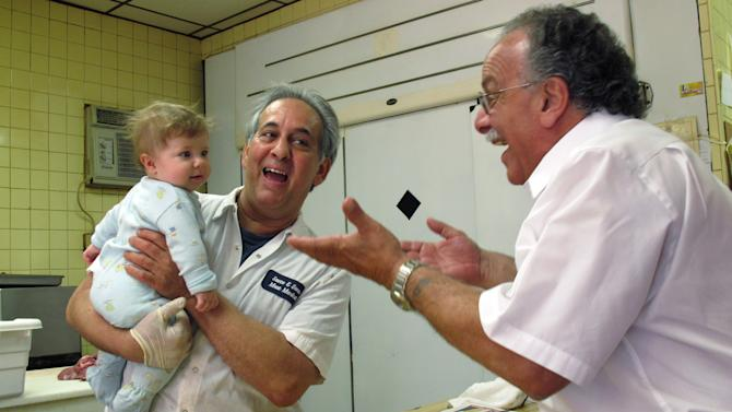 """John Sacco Sr. hands his 6-month-old grandson, Jack Russo, to Pete Canu, a customer in Sacco's Elizabeth, N.J., butcher shop, Thursday, June 20, 2013. Canu says he liked the realism and human flaws of actor James Gandolfini's Tony Soprano character, but Sacco said, """"The Sopranos perpetuated and spread negative stereotypes about Italian-Americans."""" Gandolfini died June 19, in Italy, and is being remembered in the northern New Jersey towns where the show was filmed. (AP Photo/Wayne Parry)"""