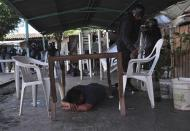 An inmate lies under a table as riot policemen inspect an area after a gunfight in the Tuxpan prison in Iguala, in the Mexican State of Guerrero January 3, 2014. REUTERS/Jesus Solano