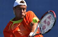 Lleyton Hewitt of Australia returns to Gilles Muller of Luxembourg during their 2012 US Open men's singles match at the USTA Billie Jean King National Tennis Center in New York. Hewitt beat Muller 3-6, 7-6 (7/5), 6-7 (5/7), 7-5, 6-4