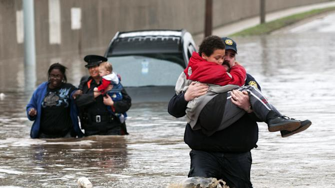 Firefighter Jason Kelley and police officer Shannon Vandenheuvel carry children from Barbara Jones' partially submerged car  in Grand Rapids, Mich. Thursday, April 18, 2013. Middle America was getting everything nature has to throw at it on Thursday, from snow in the north to tornadoes in the Plains, and with torrential rains causing floods and transportation chaos in several states. (AP Photo/Grand Rapids Press, Chris Clark)