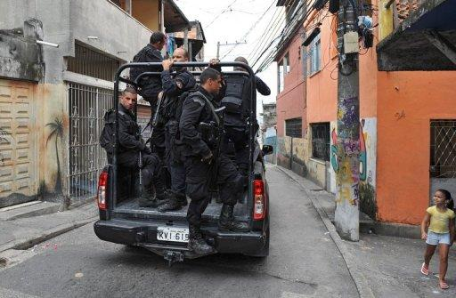 Policemen of the Special Operations Battalion patrol a street at Ilha do Governador neighborhood, January 24, 2013