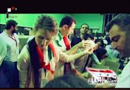 An image grab taken off the official Syrian TV shows President Bashar al-Assad (C) and his wife Asma joining volunteers as they pack boxes at a food distribution center set up at the Al-Fahya stadium in Damascus for victims of fighting in the central restive city Homs