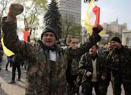 An Ukrainian activist shouts a slogan during a rally outside the parliament in Kiev, Ukraine, Tuesday, April 15, 2014. Pro-Russian insurgents who have seized government buildings across eastern Ukraine dug in on Tuesday, fortifying their positions and erecting fresh barricades. (AP Photo/Sergei Chuzavkov)