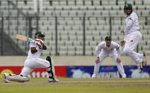 Bangladesh's Imrul Kayes, left, plays a shot, as South Africa's Temba Bavuma, right, jumps during their first day of the second cricket test match in Dhaka, Bangladesh, Thursday, July 30, 2015. (AP Ph