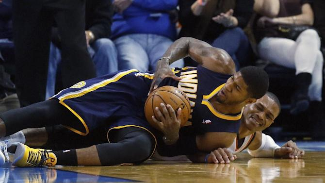 Indiana Pacers forward Paul George (24) keeps the ball away from Oklahoma City Thunder guard Russell Westbrook (0) in the third quarter of an NBA basketball game in Oklahoma City, Sunday, Dec. 8, 2013. Oklahoma City won 118-94