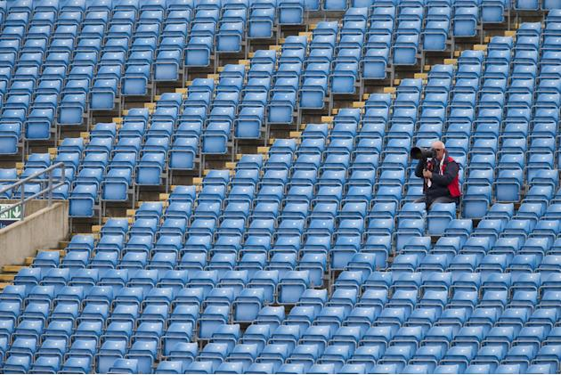 A photographer sits in nearly empty stands on the fifth day of the second Test match between England and New Zealand at Headingley cricket ground in Leeds, England, Tuesday, June 2, 2015. (AP Photo/Jo