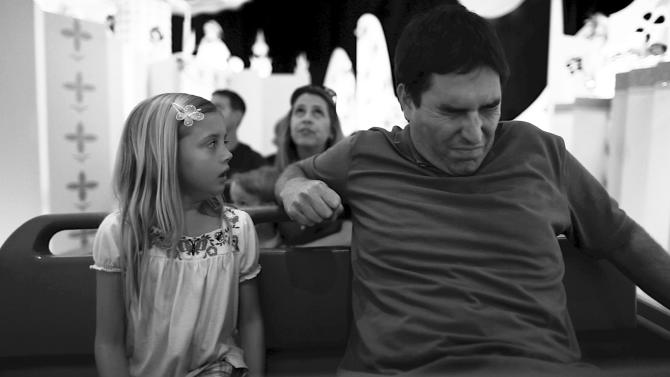 """This undated photo released by Mankurt Media, LLC shows Roy Abramsohn as Jim freaking out during a ride in the amusement park on the last day of his family vacation in a scene from """"Escape from Tomorrow,"""" a feature film by writer/director Randy Moore. As an adult, and a filmmaker, Moore wanted to capture and question the allure of manufactured-fantasy theme parks. (AP Photo/Copyright Mankurt Media, LLC)"""