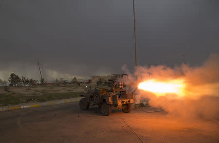 Shi'ite fighters fire a rocket during clashes with Islamic State militants in Salahuddin province