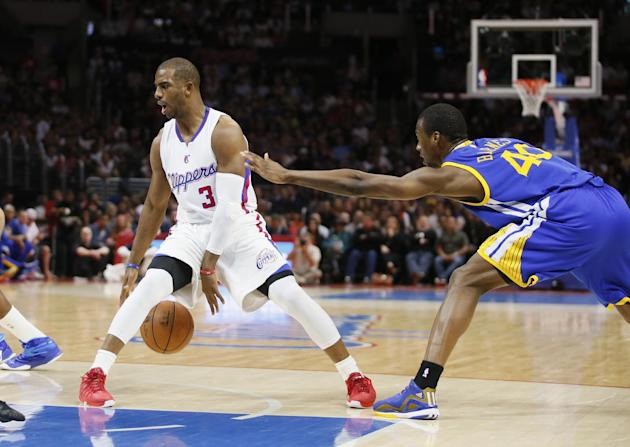 Los Angeles Clippers Chris Paul, left, dribbles between his legs while Golden State Warriors' Harrison Barnes, right, defends during the first half of an NBA basketball game, Tuesday, March 31, 20