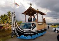 Britain's Prince William and his wife Catherine (centre R), the Duchess of Cambridge, wave to Solomon Islanders as they leave the airport aboard a truck decorated as canoe in Honiara on September 16, 2012. The royal couple are on a nine-day tour marking Queen Elizabeth II's Diamond Jubilee, and have already visited Singapore and Malaysia before arriving in the Solomon Islands