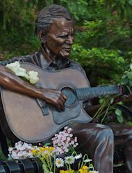 """In this photo provided by Mast General Store, flowers adorn a statue of Arthel """"Doc"""" Watson in downtown Boone, N.C., on Friday, May 25, 2012. The Grammy-winning folk musician Doc Watson is in critical condition but improving at a North Carolina hospital after colon surgery. (AP Photo/Mast General Store, Lynn Willis)"""