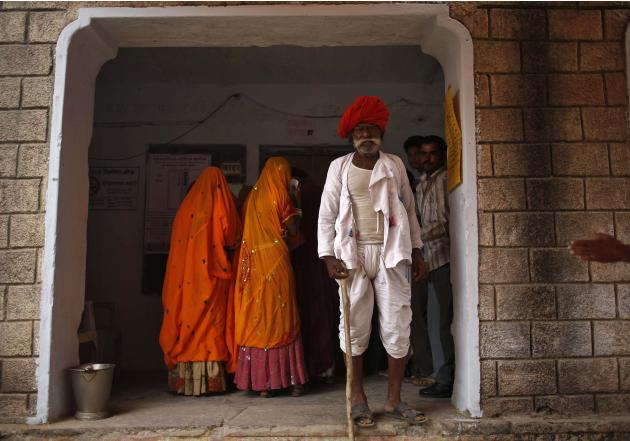 Man wearing a traditional turban looks on after casting his vote outside a polling station in Ajmer