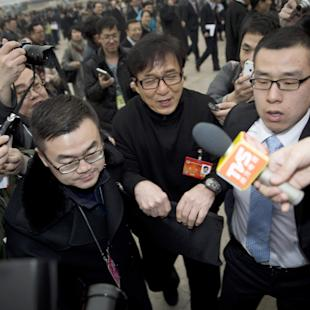 "FILE - In this March 3, 2014 file photo, Hong Kong movie star Jackie Chan, center, is escorted by officials as he is surrounded by journalists upon arrival at the Great Hall of the People to attend the opening session of the Chinese People's Political Consultative Conference (CPPCC) in Beijing. Jackie Chan might still be popular in China, but nowadays the pro-Beijing actor is as well-known as fodder for jokes as he is for his gritty martial arts and slapstick humor on screen. His latest contribution to the country's mass culture and entertainment: ""duang."" It's not a word, but a sound he made in an old TV commercial meaning something like ""ta-da!"" A new mash-up video of the old ad has made ""duang"" a trending topic on China's social media. (AP Photo/Andy Wong, File)"