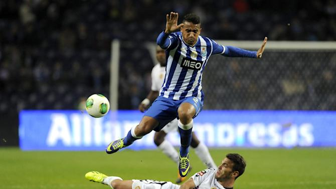 Nacional's Nuno Sequeira, on the pitch, clears the ball from FC Porto's Danilo Silva, from Brazil, in a Portuguese League soccer match at the Dragao stadium in Porto, Portugal, Saturday, Nov. 23, 2013. The match ended in a 1-1 draw