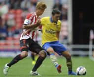 Arsenal's Mesut Ozil (R) is challenged by Sunderland's Ki Sung-Yeung during their English Premier League soccer match at The Stadium of Light in Sunderland, northern England, September 14, 2013. REUTERS/Nigel Roddis