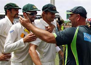 Australia's Mitchell Johnson (L), Nathan Lyon (2nd L) and Shane Watson prepare to hug coach Darren Lehmann after winning the Ashes test cricket series against England at the WACA ground in Perth December 17, 2013. REUTERS/David Gray