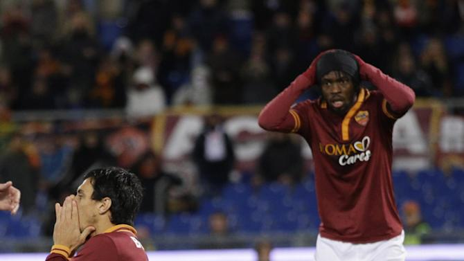 AS Roma defender Nicolas Burdisso, of Argentina, left, kneels on the ground after he failed a scoring chance, as his teammate Gervinho, of Ivory Coast, touches his head during a Serie A soccer match between As Roma and Cagliari, at Rome's Olympic stadium, Monday, Nov. 25, 2013. The match ended in a scoreless tie