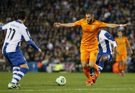 Real Madrid's Karim Benzema is challenged by Espanyol's Joan Capdevila and Sidnei Rechel during the King's Cup soccer match at Cornella El Prat stadium, in Barcelona
